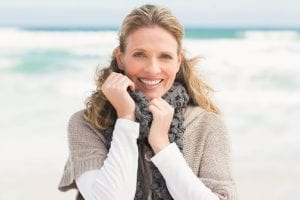 Woman in winter clothing on the beach