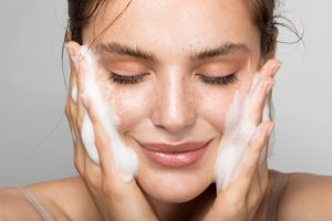 Woman washing her face as part of her morning skin care routine