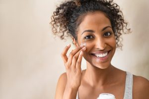 Woman applying moisturizer as part of her skin care routine