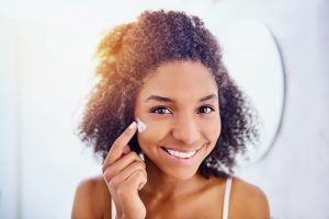 Young Black woman applying skin cream