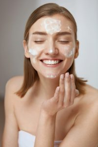 A woman washes her face with facial cleanser.