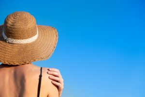 Woman in straw hat in sun.