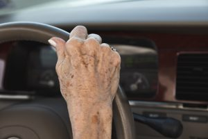 Woman's hand on steering wheel with age spots