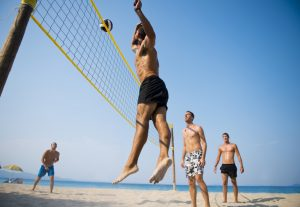 Young men playing beach volleyball.