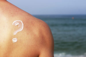 Man with sunscreen on his back in the shape of a question mark.