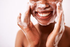 Woman washing her face with a foaming cleanser to prevent oily skin